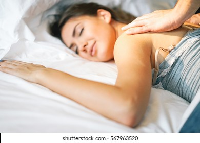 Beautiful young woman relaxing while her boyfriend is giving her a massage on the bed whit white sheets - Peaceful and tender moments of a couple in love in the bed - Focus on male hand