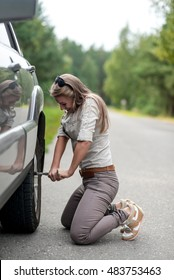A beautiful young woman repairing a car, unscrew the wheel