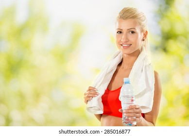 Beautiful young woman resting after a set of exercises with a bottle of water. Looking at camera.