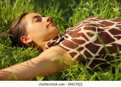 Beautiful young woman resting in green grass