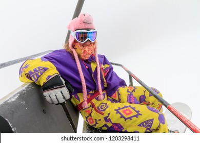 Beautiful young woman in retro vintage outfit in the chairlift on a foggy winter day in the Alps in the Brandnertal, Vorarlberg Austria