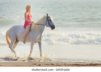 Beautiful young woman riding a horse along the beach, she is happy of her hobby