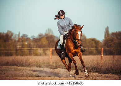 a beautiful young woman riding a horse in a black helmet and boots