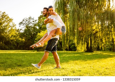 A beautiful young woman riding on her boyfriends back on a field in the sunset