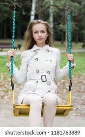 beautiful young woman is riding in the park on a swing, summer time