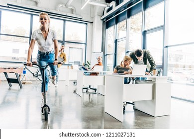 beautiful young woman riding scooter at modern open space office