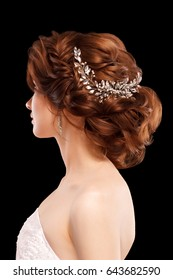 Beautiful young woman with romantic wedding hairstyle isolated on black background