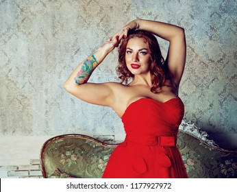 beautiful young woman with rose tatoo, wearing a red dress