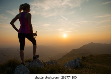 beautiful young woman run on a mountain path at sunrise