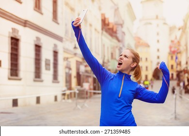 Beautiful young woman running in the city race taking a selfie