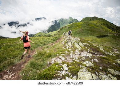 beautiful young woman running fast on the mountain trail over peaks with sky and clouds view