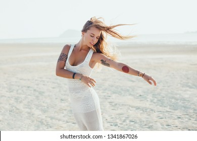 Beautiful young woman running on the beach with a yellow tissue. Happy smiling girl with scarf enjoying at beach. Freedom and carefree concept, tattoo, wild hair, Bali, close, dress