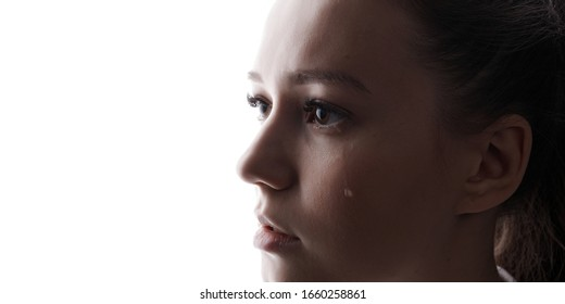 Beautiful young woman with sad big eyes crying. White background. Free space for text. Tear on cheek of unhappy female.