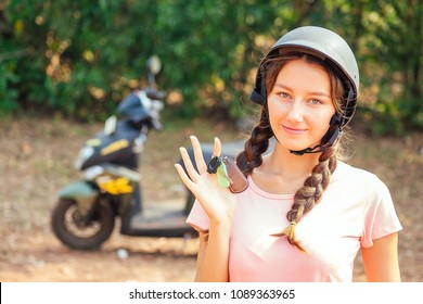 beautiful and young woman in a safety helmet sitting on a motorcycle (bike) and holds the keys. concept of safe driving a scooter and renting in Asia