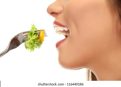 beautiful young woman with  salad on fork, isolated on white