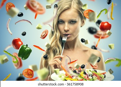 Beautiful young woman with salad on blue background, flying vegetables and fruit, Portrait of a beautiful young woman eating vegetable salad. Isolated over blue background.