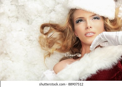 Beautiful young woman in Santa Claus clothes lying in snow.
