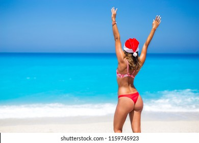 Beautiful young woman with santa hat on the beach looking into the ocean photographed from behind