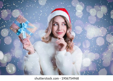 Beautiful young woman in Santa hat with Christmas present on color background