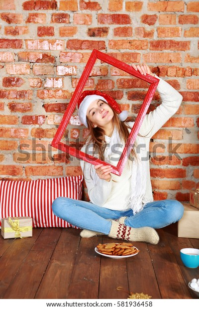 Beautiful young woman in santa hat sitting with crossed legs in santa hat