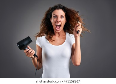 A beautiful young woman screaming while using a hairdryer and a hairbrush.