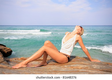 Beautiful young woman in the sea spashing water