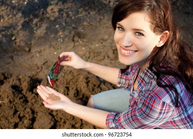 Beautiful young woman with seeds in her hand