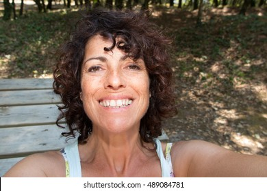 Beautiful young woman selfie in the park with a smartphone