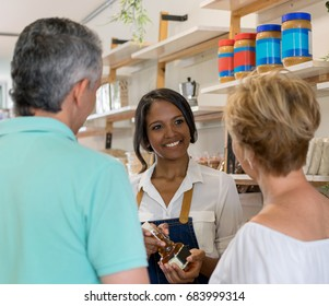 Beautiful young woman selling olive oil to an adult couple looking for healthy food at a supermarket