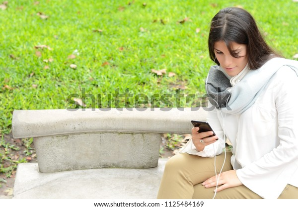 beautiful young woman sending message with smartphone on the street.