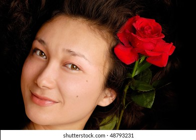Beautiful young woman serene face with a red rose