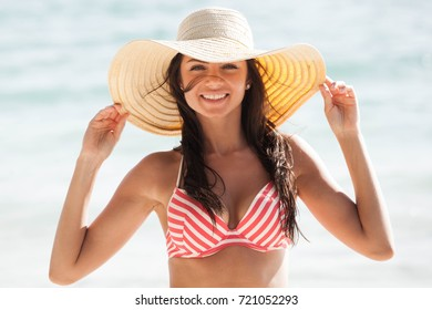 Beautiful young woman in sexy bikini and sunhat standing at sea beach