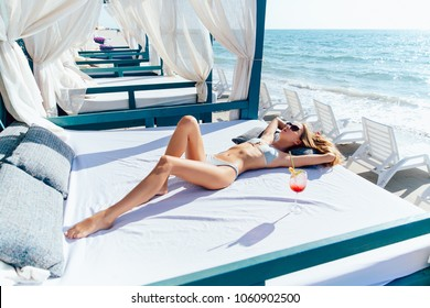 Beautiful young woman with sexy body in sunglasses and swimsuit, takes a sunbath while relaxing on a luxury sunbed, near the ocean.