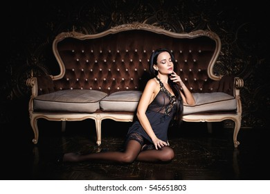 Beautiful young woman in a sexy peignoir on sofa