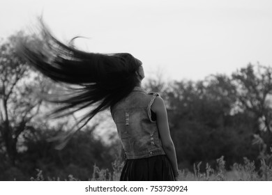 beautiful young woman shaking her long hair from back in the autumn field at sunset, state of meditation, feeling of freedom, be yourself, monochrome