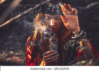 beautiful young woman with shamanic fire outdoors