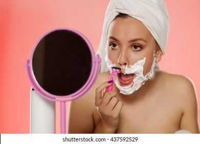 beautiful young woman shaving her face with foam and razor