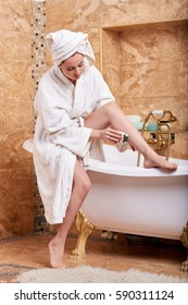 Beautiful young woman shaving her legs in bathroom. Concept of body care.