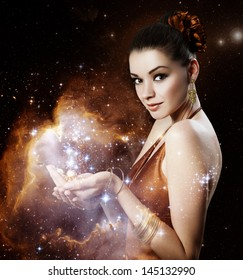 Beautiful young woman with shiny magic gift - gold portrait.Elements of this image furnished by NASA