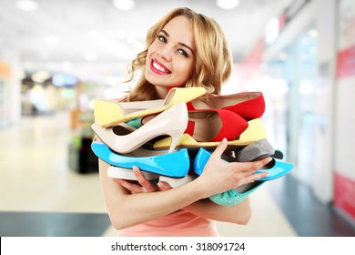 Beautiful young woman with shoes in the mall