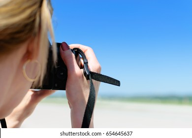 Beautiful young woman shoots a photo on the beach with a professional DSLR camera.