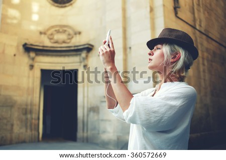 Beautiful young woman shoots video via mobile phone camera during excursion near vintage building outside,stylish female tourist making photo of architectural monument during while touring in the city