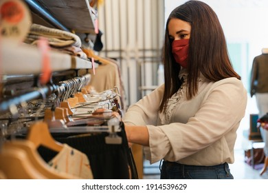 Beautiful young woman in shop looks at clothes to buy wearing protective face mask during Coronavirus pandemic Covid-19 - Shop assistant arranges dress