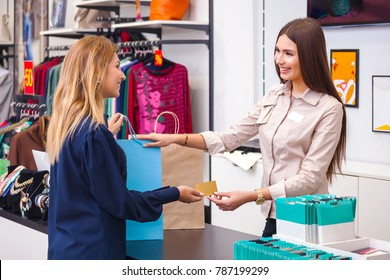 Beautiful young woman with shopping bag giving her credit card to seller in clothing shop