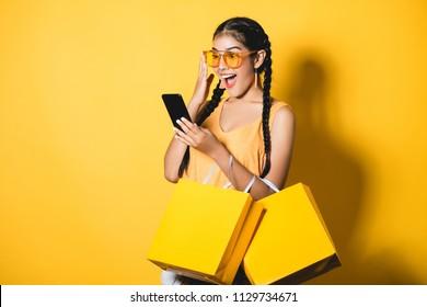 Beautiful young woman with shopping bags using her smart phone on yellow background.Shopaholic shopping Fashion.
