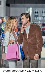 beautiful young woman with shopping bags able to kiss smiling man in boutique