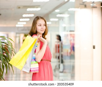 Beautiful young woman with shopping bags in a supermarket