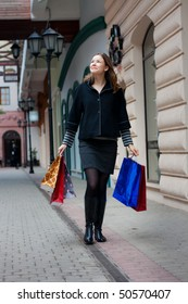 beautiful young woman with shopping bags walking outdoors