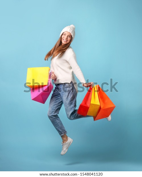 Beautiful young woman with shopping bags jumping on blue background