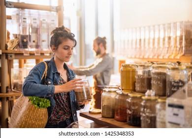 Schöne junge Frau, die in einem großen Lebensmittelgeschäft einkauft. Sie kauft organische Gewürze in Gläsern